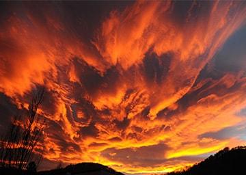 Blick in den Himmel, dessen Wolken rot gefärbt sind