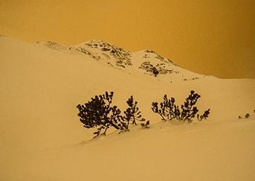Blick auf einen schneebdeckten Hügel, der rötlich gefärbt ist