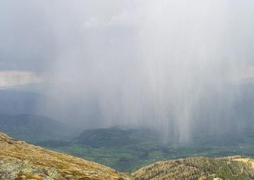 Blick von Berg ins Tal, über dem es gerade regnet