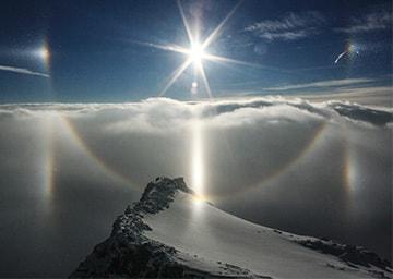 Blick über einer Wolkendecke zur Sonne. Ein Kreis zieht sich um die Sonne