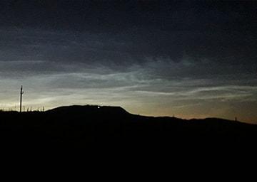Blick in den Nachthimmel, auf dem leuchtende Wolken erkennbar sind