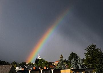 Ein leuchtender Regenbogen über einer kleinen Stadt