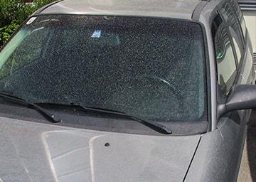 Rötlicher Staub auf einer Fensterscheibe eines Autos