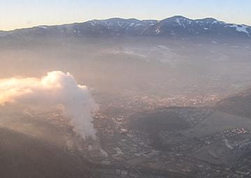 Blick über eine Stadt und Rauch aus einem Industriegebiet